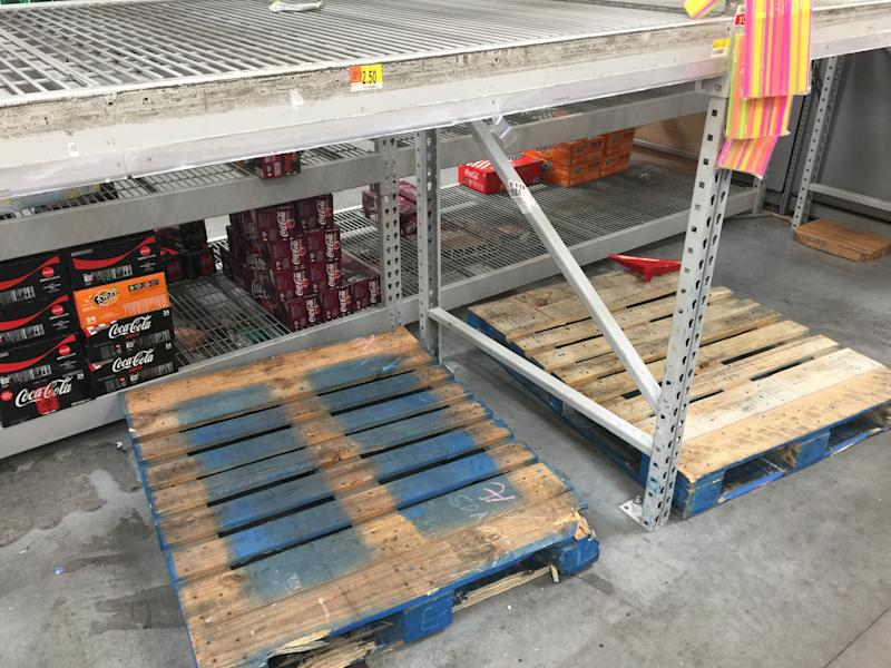 Wooden pallets and shelves that used to hold stacks of bottled water are empty at a Walmart in Fort Lauderdale on Wednesday. (Travis Waldron/HuffPost)