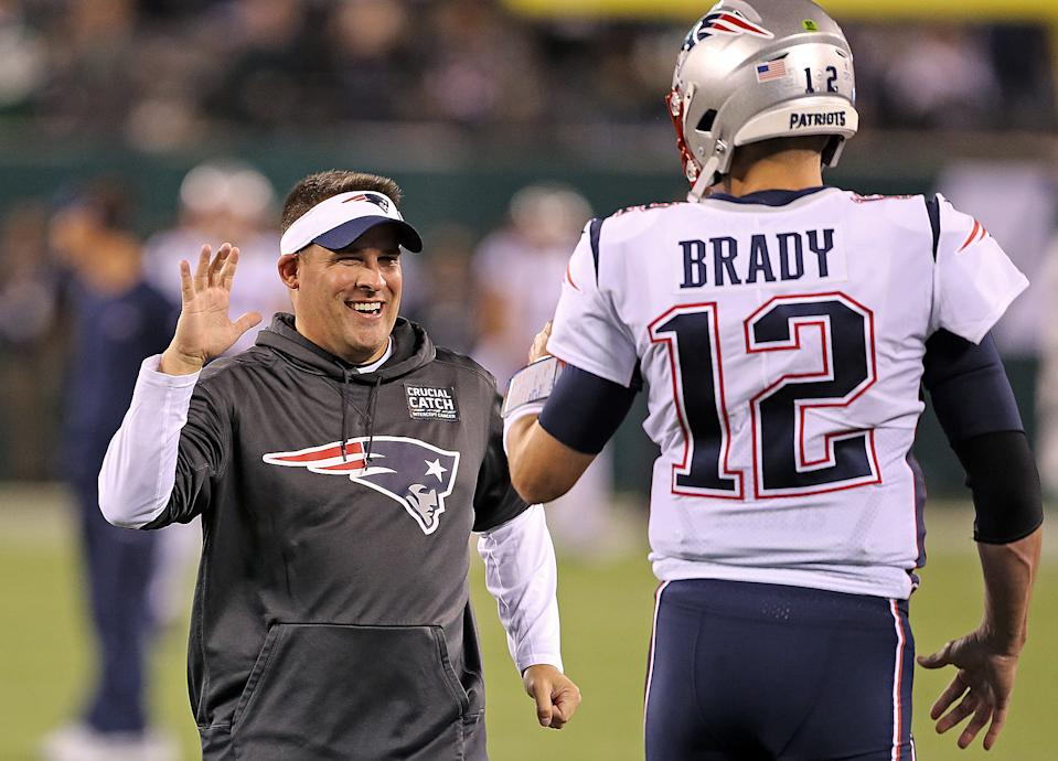 New England Patriots offensive coordinator Josh McDaniels high fives Tom Brady before their game against the New York Jets at MetLife Stadium on Oct. 21, 2019, in East Rutherford, New Jersey. (Matt Stone/MediaNews Group/Boston Herald)