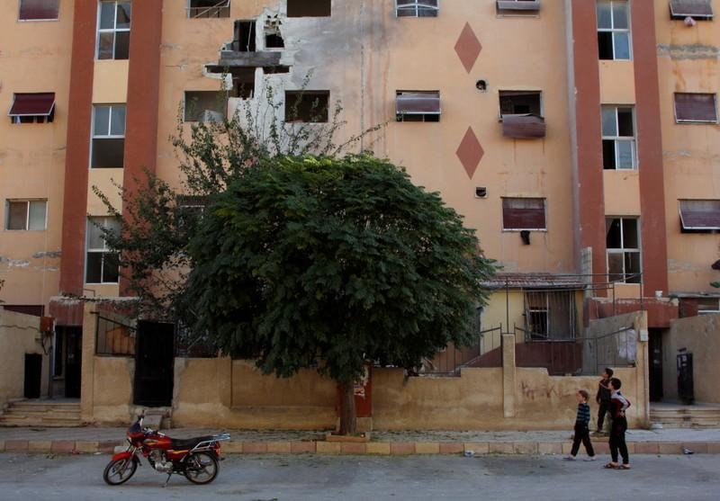 Boys stand near a building, damaged by an Israeli attack in Damascus