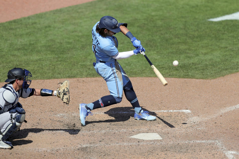 Toronto Blue Jays' Bo Bichette connects on a game-winning home run in front of New York Yankees catcher Kyle Higashioka during the ninth inning of a baseball game Wednesday, April 14, 2021, in Dunedin, Fla. The Blue Jays won 5-4. (AP Photo/Mike Carlson)