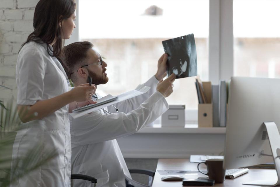 Doctors discussing intestines x-ray at medical office
