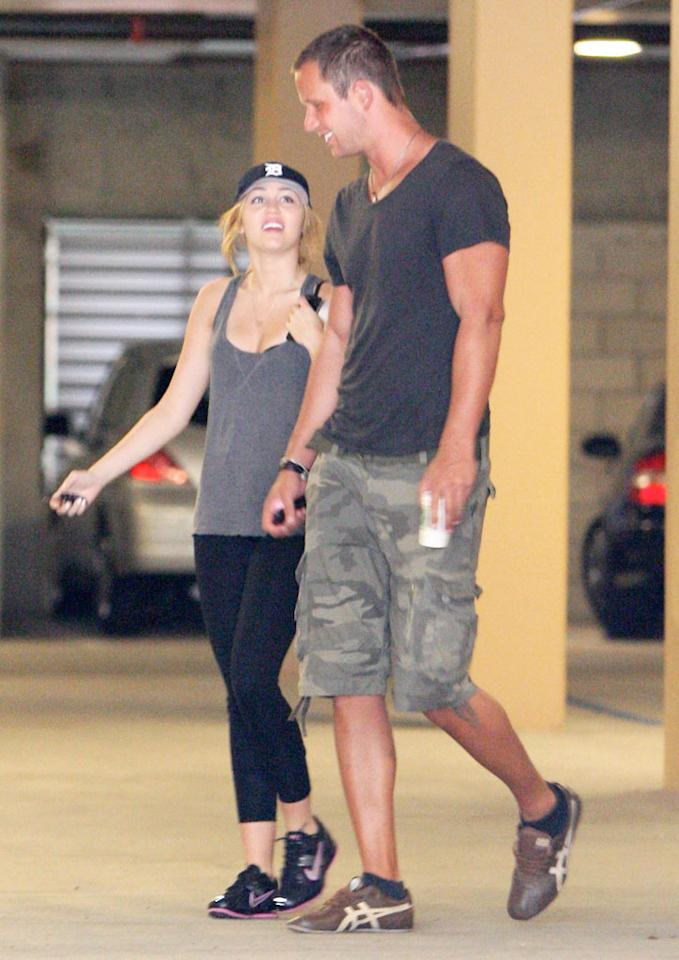 """According to X17Online, after recently working out in L.A., Cyrus was """"spotted giggling and getting a little touchy-feely"""" with an unidentified, tall """"hot new hunk."""" So, who is this guy and how long have they been together? For the exclusive answer, click over to <a href=""""http://www.gossipcop.com/miley-cyrus-new-guy-flirting-trainer-liam-hemsworth/"""" target=""""new"""">Gossip Cop</a>. Fabio/<a href=""""http://www.x17online.com"""" target=""""new"""">X17 Online</a> - October 1, 2010"""