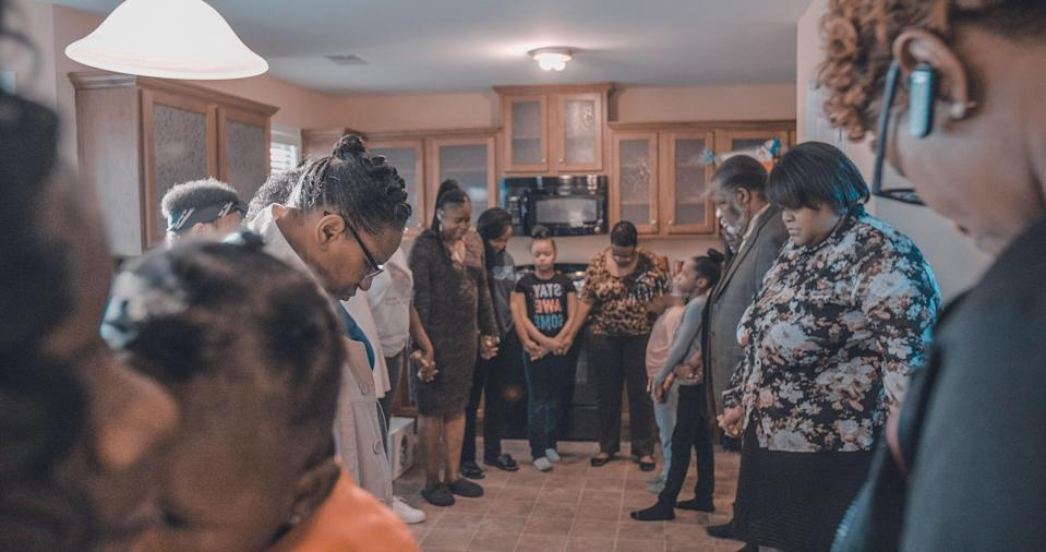 """<div class=""""caption""""> The Coggins family prays before eating a meal together in 2018 at a family member's house in Spalding County, Georgia. </div> <cite class=""""credit"""">Courtesy of Observatory Productions</cite>"""