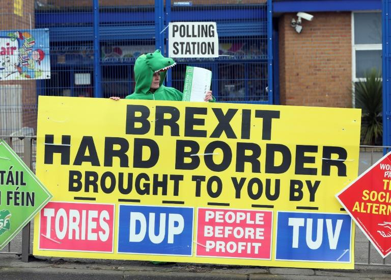 A Sinn Fein party election worker holds a Brexit banner outside a polling station in Belfast on March 2, 2017