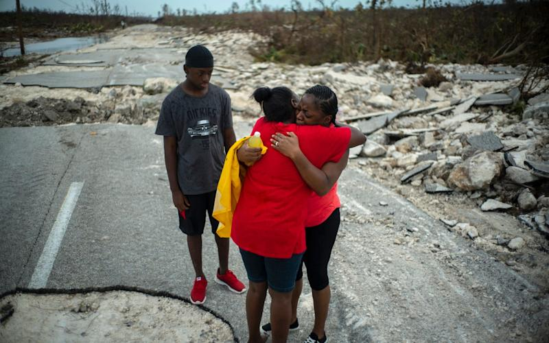 Hurricane survivors search for relatives on a shatter road in Grand Bahama - AP