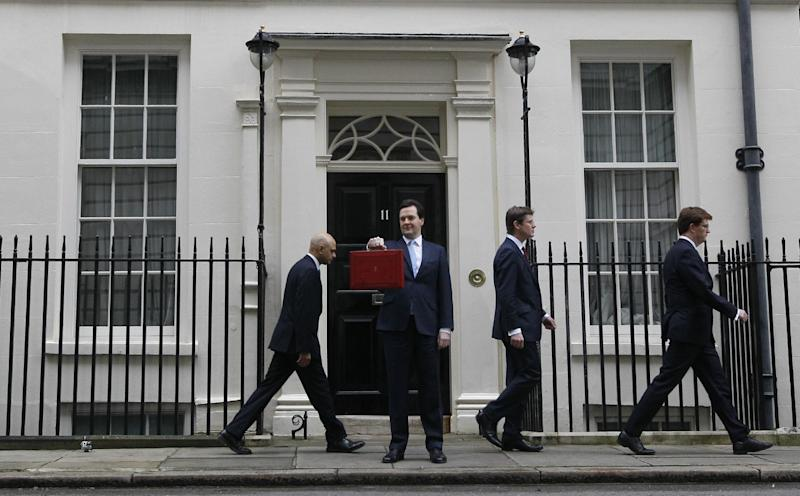 Britain's Chancellor George Osborne holds up his brief case for the media as Treasury team members walks away from 11 Downing Street , as he leaves to attend Parliament in London, Wednesday, March 20, 2013. Later Wednesday Britain's Chancellor George Osborne will deliver the Spring Budget Statement in Parliament. (AP Photo/Kirsty Wigglesworth)