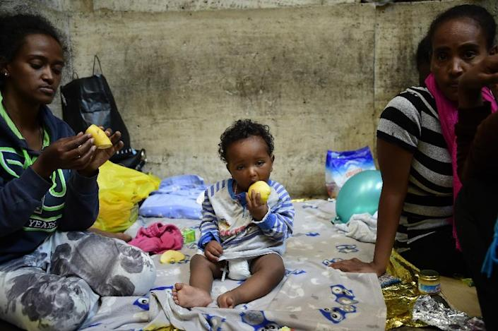 Ten-month-old Dan from Eritrea waits for food and supplies with his relatives a train station in Milan, Italy, on June 11, 2015 (AFP Photo/Olivier Morin)