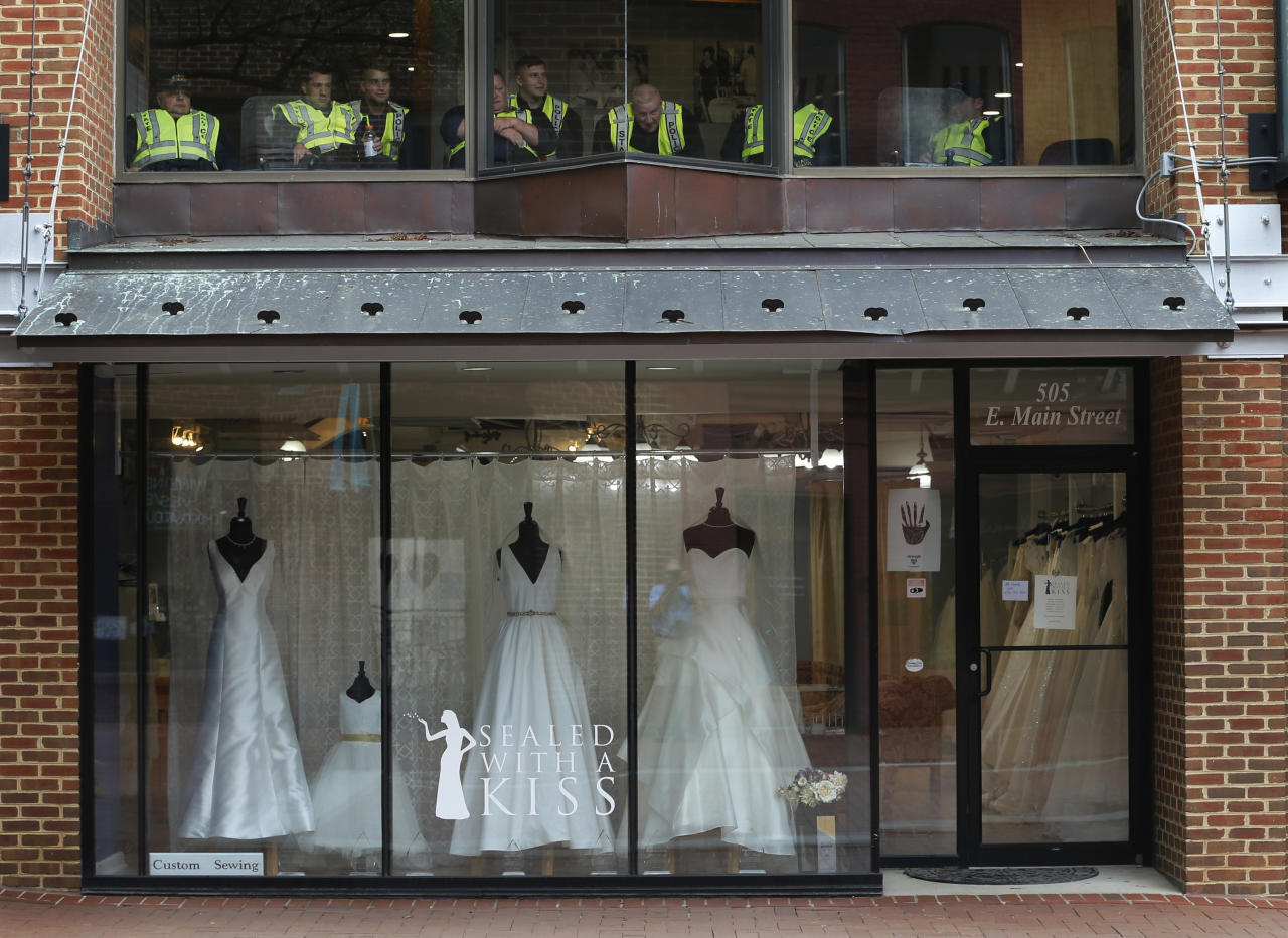 <p>State Police take a break in an office above a closed bridal shop in the downtown area of Charlottesville, Va., Saturday, Aug. 11, 2018. (Photo: Steve Helber/AP) </p>