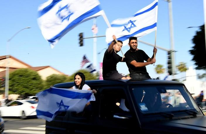 """Demonstrators in Beverly Hills wave Israeli flags during a protest against antisemitism on May 23. <span class=""""copyright"""">(Los Angeles Times)</span>"""
