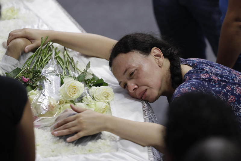 A relative mourns 15-year-old Caio Oliveira, a victim of a mass shooting at the Raul Brasil State School, in Suzano, Brazil, Thursday, March 14, 2019. Classmates, friends and families began saying goodbye on Thursday, with thousands attending a wake in the Sao Paulo suburb while authorities worked to understand what drove two former students to attack the school with a gun, crossbows and small axes. (AP Photo/Andre Penner)