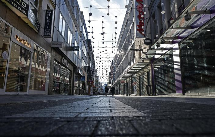 FILE - In this Dec. 16, 2020 file photo, people walk in a shopping road during the lockdown in Cologne Germany. Germany's leading economic institutes has downgraded their forecast for Europe's biggest economy saying it is still shaped by the impact of the coronavirus pandemic and that global supply bottlenecks also hamper the country's recovery. (AP Photo/Martin Meissner, File)