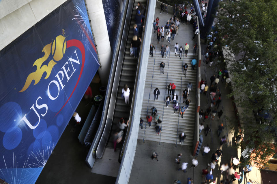 FILE - In this Sept. 3, 2017, file photo, tennis fans move in and out of Arthur Ashe Stadium during the fourth round of the U.S. Open tennis tournament in New York. How much does each first-round loser in singles at the U.S. Open take home in prize money? Who holds the women's record for most aces in the tournament? See how much you know about the year's last Grand Slam tennis tournament by taking the AP's U.S. Open quiz. (AP Photo/Frank Franklin II, File)