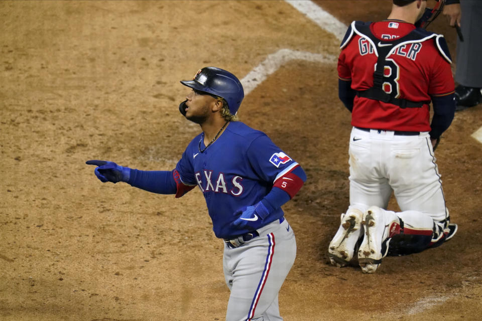 Texas Rangers' Willie Calhoun scores on a solo home run in the ninth inning of a baseball game, Tuesday, May 4, 2021, in Minneapolis. (AP Photo/Jim Mone)