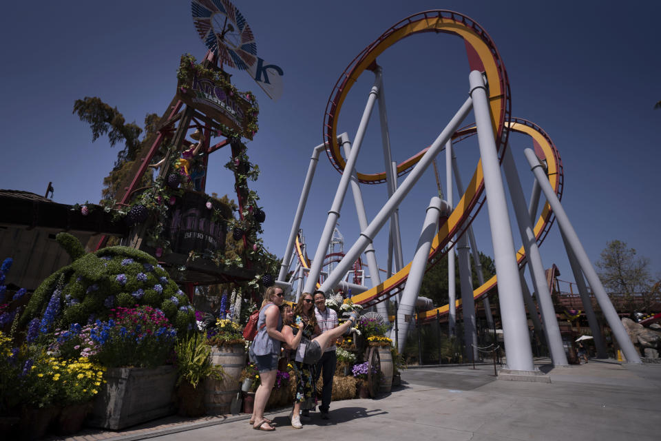 FILE - In this March 30, 2021 file photo, visitors pose for photos during the Knott's Taste of Boysenberry Festival at Knott's Berry Farm in Buena Park, Calif. California will allow indoor concerts, theater performances and other private gatherings starting April 15, 2021, as the rate of people testing positive for the coronavirus in the state nears a record low. (AP Photo/Jae C. Hong, File)