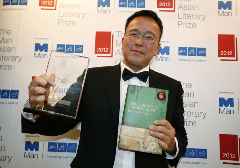 "Malaysian author Tan Twan Eng poses after his novel ""The Garden of Evening Mists"" won the 2012 Man Asian Literary Prize in Hong Kong Thursday, March 14, 2013. The book beat four others Thursday night to win the $30,000 award, one of Asia's most prestigious. Tan's book is only the second winner to be written in English.  (AP Photo/Vincent Yu)"