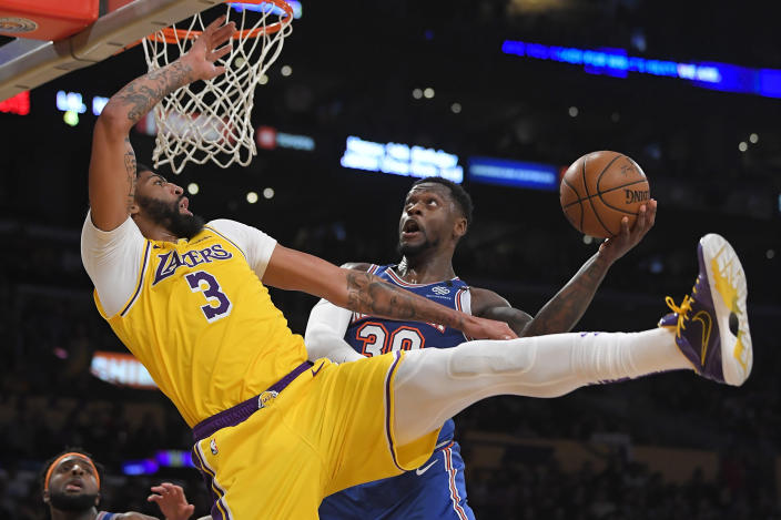 New York Knicks forward Julius Randle, right, shoots as Los Angeles Lakers forward Anthony Davis defends during the second half of an NBA basketball game Tuesday, Jan. 7, 2020, in Los Angeles. Davis was injured on the play and left the game. (AP Photo/Mark J. Terrill)