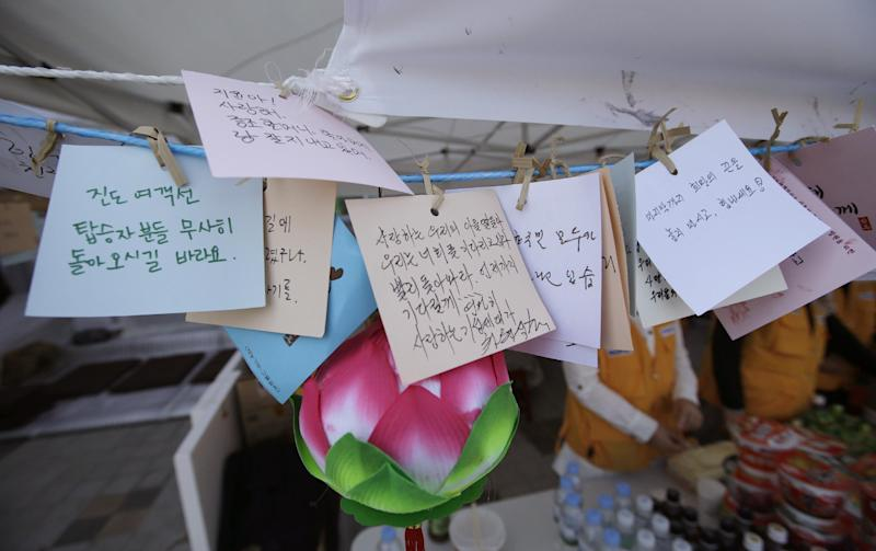 Messages wishing safe return of passengers aboard the sunken ferry Sewol hang with a Buddhism lotus decoration in Jindo, south of Seoul, South Korea, Tuesday, April 22, 2014. One by one, coast guard officers carried the newly arrived bodies covered in white sheets from a boat to a tent on the dock of this island, the first step in identifying a sharply rising number of corpses from a South Korean ferry that sank nearly a week ago. (AP Photo/Lee Jin-man)