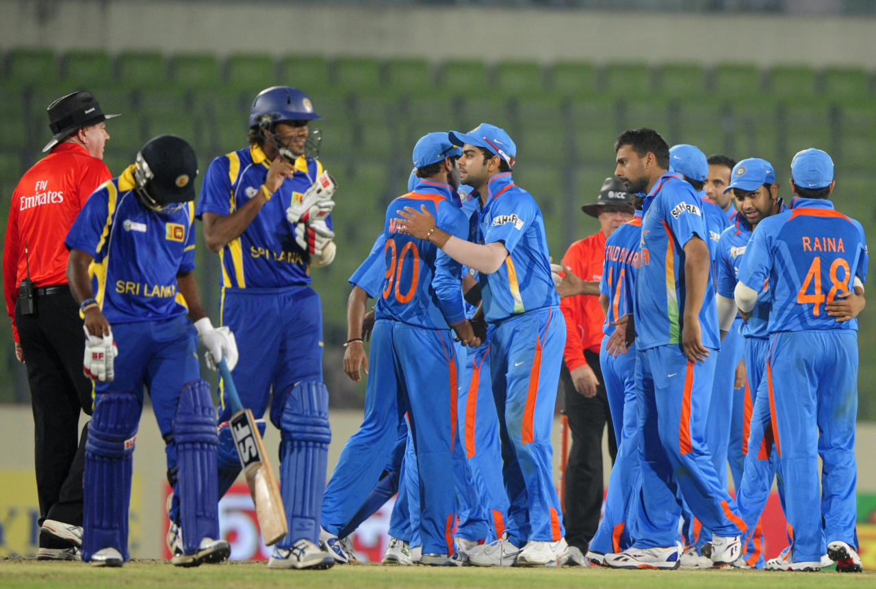 Indian cricketers celebrate their victory as Sri Lankan cricketers Suranga Lakmal (2nd L) and Seekkuge Prasanna (L) leave the field during the one day international (ODI) Asia Cup cricket match between India and Sri Lanka at The Sher-e-Bangla National Cricket Stadium in Dhaka on March 13, 2012.