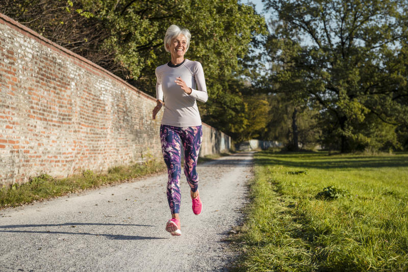 Senior woman running along brick wall in a park