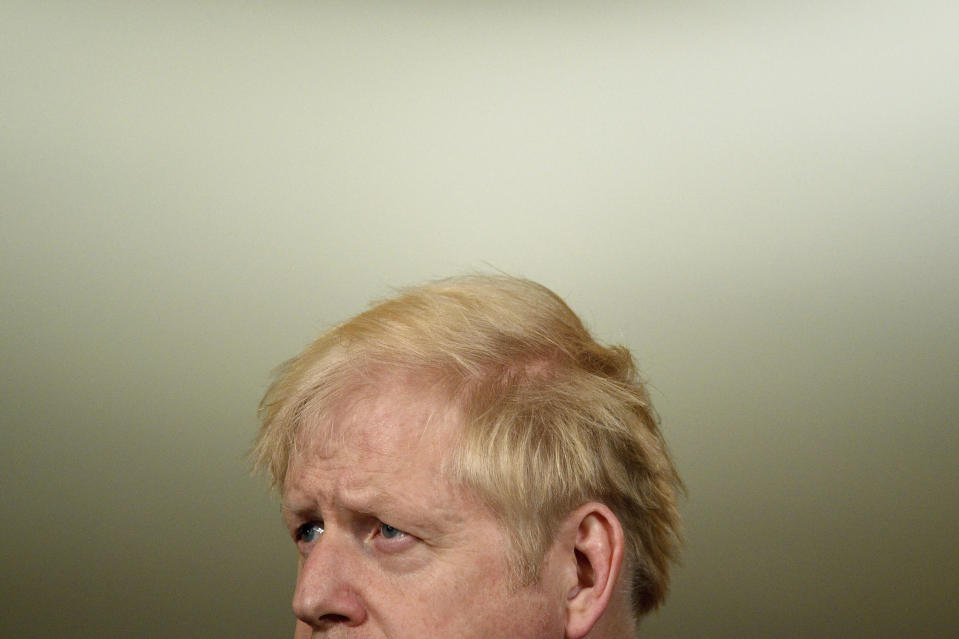 Britain's Prime Minister Boris Johnson pauses, during a coronavirus media briefing in Downing Street, London, Tuesday, Oct. 20, 2020. British Prime Minister Boris Johnson says he is imposing the highest level of coronavirus restrictions on the Greater Manchester region, after days-long negotiations between his government and local leaders who reject the measures broke down with no deal reached. (Leon Neal/Pool Photo via AP)