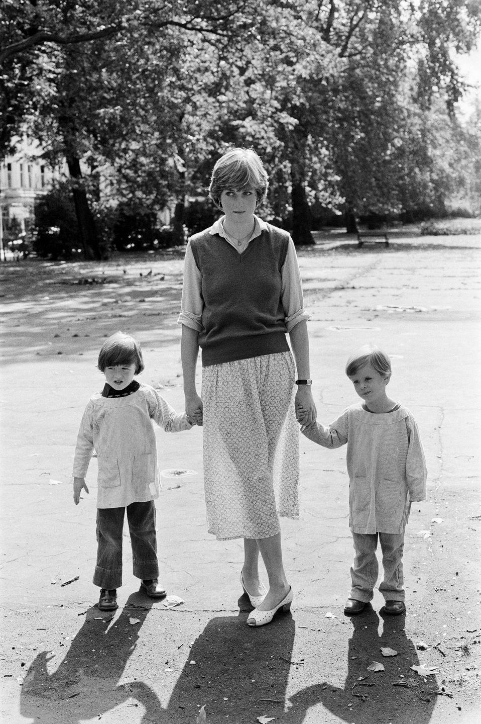 <p>Holding hands with children at the nursery school in Pimlico, London, where Diana worked as a teacher at the time.</p>