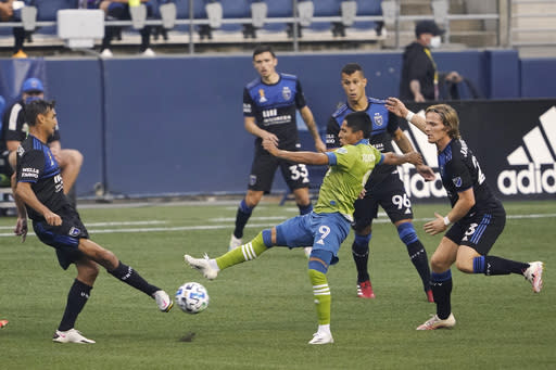 Seattle Sounders forward Raul Ruidiaz (9) kicks the ball between several San Jose Earthquakes during the first half of an MLS soccer match Thursday, Sept. 10, 2020, in Seattle. (AP Photo/Ted S. Warren)