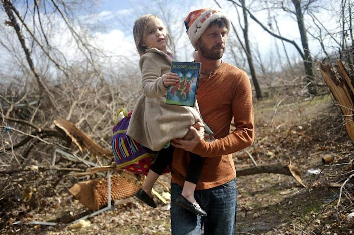 East Peoria resident Billy Vestal evacuates with his daughter, Lillian Vestal, 3, after a tornado damaged the area near Chestnut Road in East Peoria, Il.,Sunday, Nov. 17, 2013. Intense thunderstorms and tornadoes swept across the Midwest on Sunday, causing extensive damage in several central Illinois communities while sending people to their basements for shelter. (AP Photo/Journal Star, Justin Wan) MANDATORY CREDIT