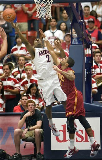 Arizona's Mark Lyons (2) shoots over the reach of Southern California's Jio Fontan (1) during the first half of an NCAA college basketball game at McKale Center in Tucson, Ariz., Saturday, Jan. 26, 2013. (AP Photo/Wily Low)
