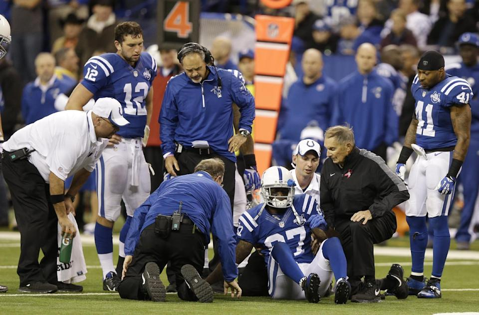 Indianapolis Colts wide receiver Reggie Wayne (87) talks to trainers as he injures his knee during the second half of an NFL football game, Sunday, Oct. 20, 2013, in Indianapolis. (AP Photo/Michael Conroy)
