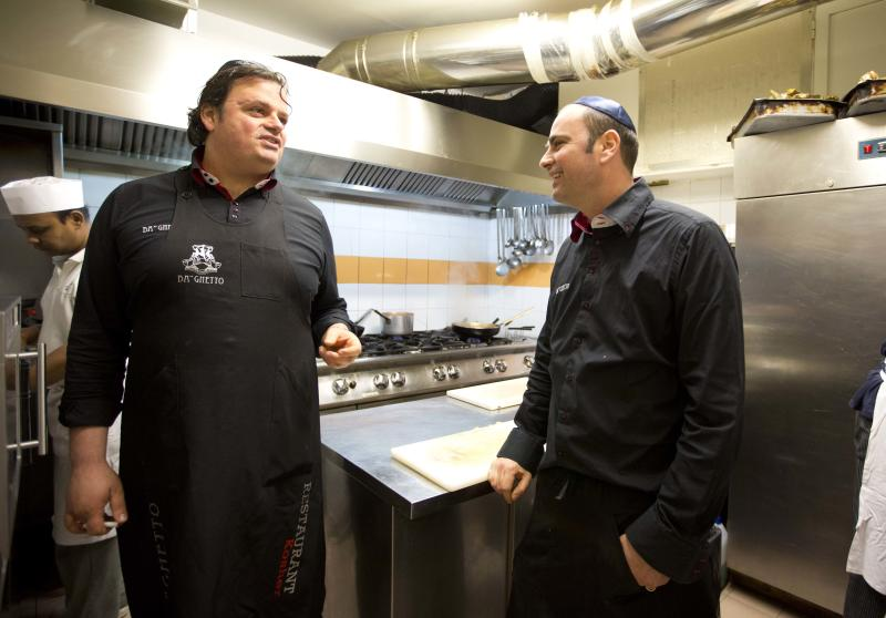 """Ba'Ghetto restaurant owners Ilan Dabush, left, and his brother Amit talk in the kitchen of their restaurant, during an interview with the Associated Press, in Rome, Monday Jan. 20, 2014. For just one day, the kitchen of the Vatican hotel where Pope Francis lives went kosher, with Rabbi Jaakov Spizzichino overseeing the scrupulous cleaning of countertops, boiling of utensils and heating of the oven necessary to render it fit for cooking under Jewish dietary laws. The occasion? A four-course luncheon Francis hosted last week for a dozen Argentine rabbis. Francis was hosting Rabbi Abraham Skorka and about 15 other rabbis from Buenos Aires who came to Rome en masse to visit their old friend, and the Vatican pulled out all the stops. Organizers turned to Ba'Ghetto, one of the best kosher restaurants in Rome's ghetto on the other side of the Tiber River, to cater the affair. """"I decided to do it simple, because the pope is simple,"""" said Amit Dabush, Ba'Ghetto's Israeli-born co-owner. """"But the menu was full: He had to make a 'bella figura,'"""" or a good impression on his guests. (AP Photo/Alessandra Tarantino)"""
