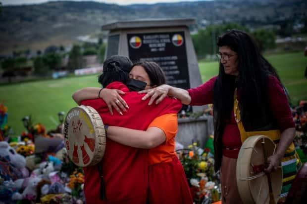 On the grounds of the former Kamloops Indian Residential School, on Tk'emlúps te Secwépemc territory, Katherine Cooper from the Mosakahiken Cree Nation in Manitoba consoles her friends at a growing memorial to honour the estimated 215 children whose remains were discovered buried in Kamloops, B.C., on June 4.  (Ben Nelms/CBC - image credit)