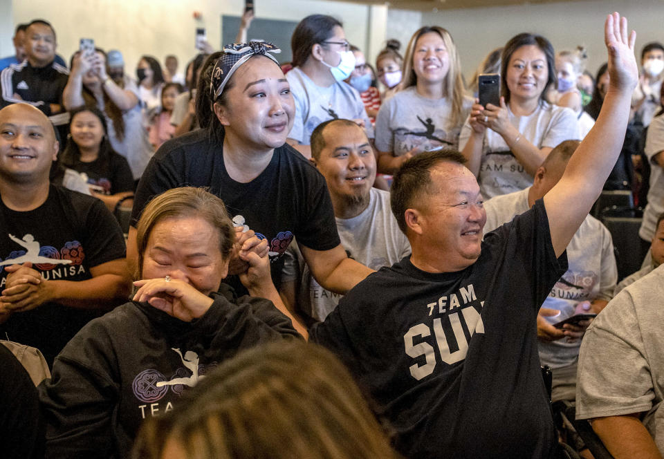 Image: Sunisa Lee's parents Yeev Thoj, left, and John Lee and other family and friends react as they watch Sunisa Lee clinch the gold medal in the women's Olympic gymnastics all-around at the Tokyo Olympics on July 29, 2021 in Oakdale, Minn. (Elizabeth Flores / Star Tribune via AP)