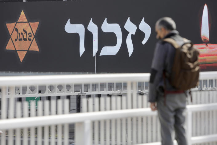 An Israeli stands as sirens mark a nationwide moment of silence in remembrance of the 6 million Jewish victims of the Holocaust, in Tel Aviv, Israel, Thursday, April 8, 2021. (AP Photo/Sebastian Scheiner)