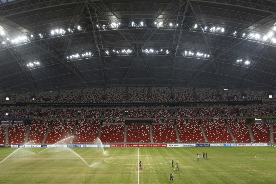 Workers maintain the pitch after a soccer training by Brazil's national team ahead of their friendly soccer match against Japan in Singapore October 13, 2014. The New Zealand Maori's non-cap rugby test against the invitational Asia Pacific Dragons in Singapore next month is in doubt as the hosts battle to repair a problematic pitch at their new National Stadium. The surface was laid in May but lacked an appropriate bedding period and has been re-seeded four times, staff said on Monday, as they try to cope with the demands of hosting so many different events in a tropical climate. The sandy pitch, with plenty of bare patches, will host Brazil in a soccer friendly against Asian Cup holders Japan on Tuesday, with organisers of the Southeast Asian soccer championships voicing concerns about Singapore's ability to part-stage their event in late November-early December. REUTERS/Edgar Su (SINGAPORE - Tags: SPORT SOCCER RUGBY)