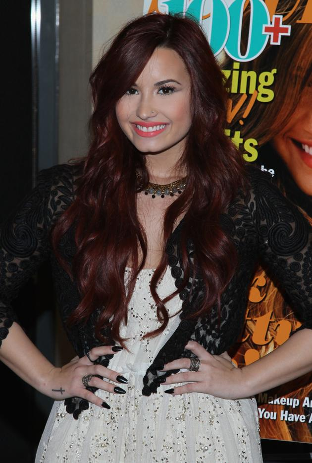 "Back in January, long before the ""X Factor"" judge shared a table with the likes of Simon Cowell, Britney Spears, and L.A. Reid, Lovato was in a darker state of mind. ""I know my hair looks black in this photo, but it was actually dark, dark red,"" says the singer, who recently partnered up with Secret deodorant on its <a href=""https://www.facebook.com/meanstinks"" target=""new"">Mean Stinks</a> campaign to end bullying. ""I was an orangey red before this, then I dyed it dark red myself."" Wait – as in <em>she</em> headed into her bathroom, donned rubber gloves, and embarked on a messy do-it-yourself job? "" Yup, I box dyed it,"" she laughs. ""With all my hair extensions it took four boxes, but I did it."""