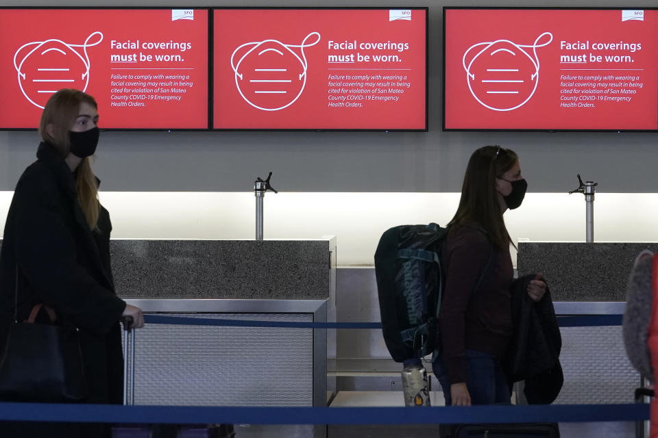 FILE— In this Dec. 22, 2020 file photo, signs advising facial covering requirements are shown as travelers stand in line at a Delta Air Lines desk at San Francisco International Airport during the coronavirus pandemic in San Francisco. Health officials in San Francisco and six other Bay Area counties announced Monday, Aug. 2, 2021 that they are reinstating a mask mandate for all indoor settings as COVID-19 infections surge because of the highly contagious delta variant. (AP Photo/Jeff Chiu, File)