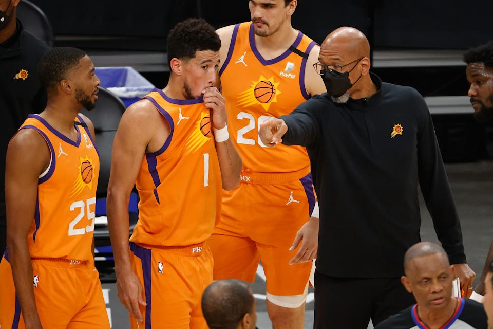Head coach Monty Williams of the Phoenix Suns talks with Devin Booker #1 and Mikal Bridges #25 during the NBA game against the Oklahoma City Thunder at Phoenix Suns Arena on April 02, 2021 in Phoenix, Arizona. The Suns defeated the Thunder 140-103. NOTE TO USER: User expressly acknowledges and agrees that, by downloading and or using this photograph, User is consenting to the terms and conditions of the Getty Images License Agreement. (Photo by Christian Petersen/Getty Images)