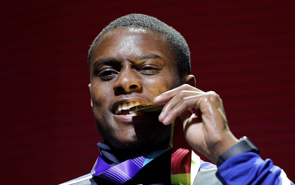 Christian Coleman of the United States, bites on his medal during ceremonies for the men's 100m at the World Athletics Championships in Doha, Qatar. - AP