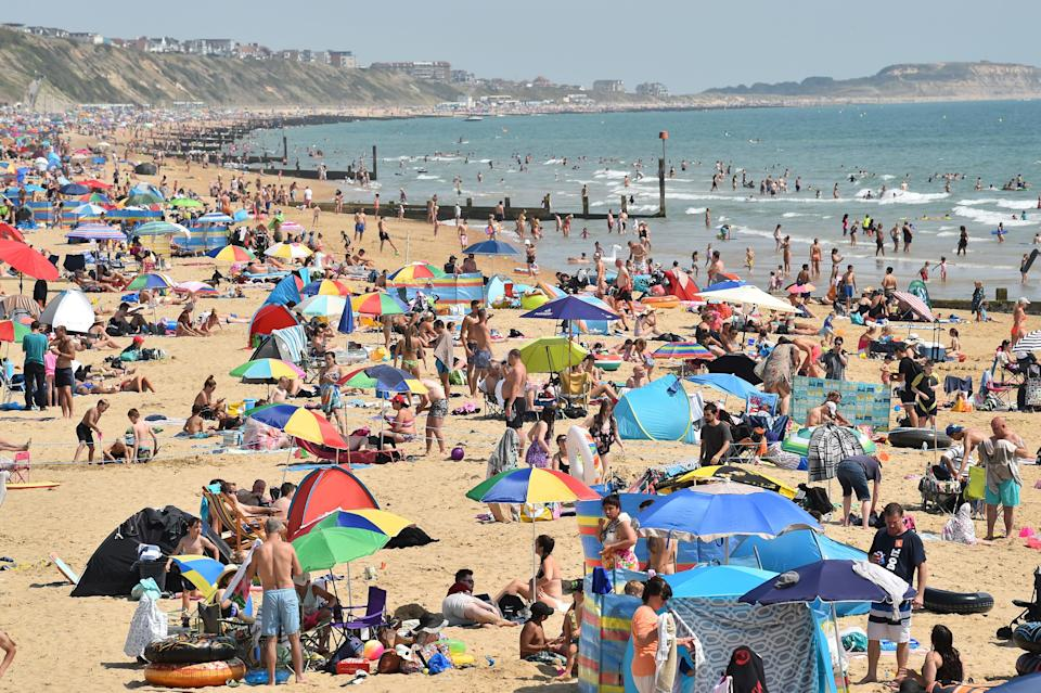 Beachgoers enjoy the sunshine as they sunbathe and play in the sea on Bournemouth beach in Bournemouth, southern England on July 31, 2020 as temperatures soar across the country. (Photo by Glyn KIRK / AFP) (Photo by GLYN KIRK/AFP via Getty Images)