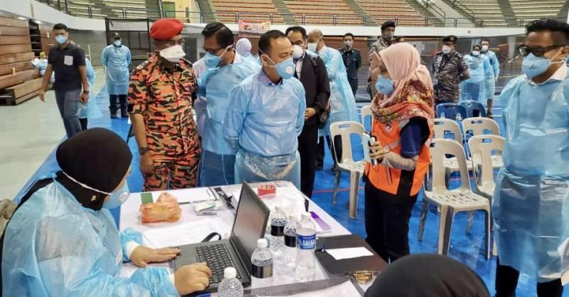 Education Minister Maszlee Malik (centre, in mask and gown) being briefed on the current situation during his visit at the Medic Base and Ground Control Centre at the Pasir Gudang Indoor Stadium today. — Picture by Ben Tan