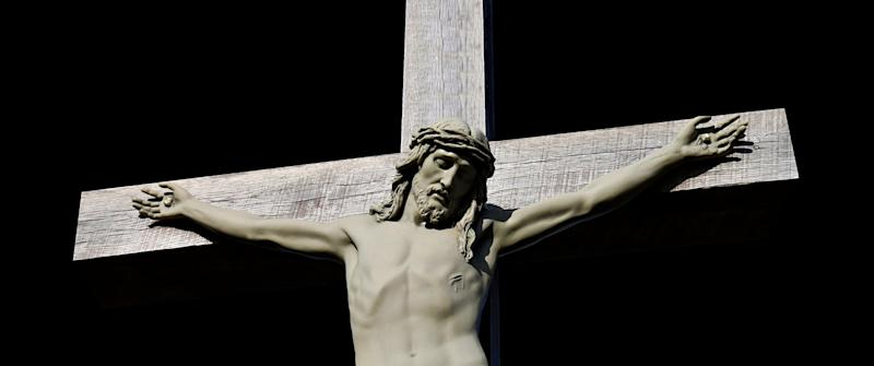 Concrete statue of crucifixion of Jesus Christ isolated on black Good Friday suffering concept