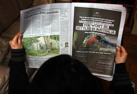 File photo of a woman reading a newspaper containing an advertisement publicising the Australian government's new policy on asylum seekers, in Sydney