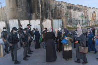 Palestinian women wait to cross the Qalandia checkpoint between the West Bank city of Ramallah and Jerusalem, to attend the first Friday prayers in al-Aqsa mosque, during the Muslim holy month of Ramadan, Friday, April 16, 2021. A limited number of Palestinian residents who carry both a travel permit and a vaccination document, are allowed to cross into Israel to attend the prayers at al-Aqsa mosque, due to the coronavirus pandemic. (AP Photo/Nasser Nasser)