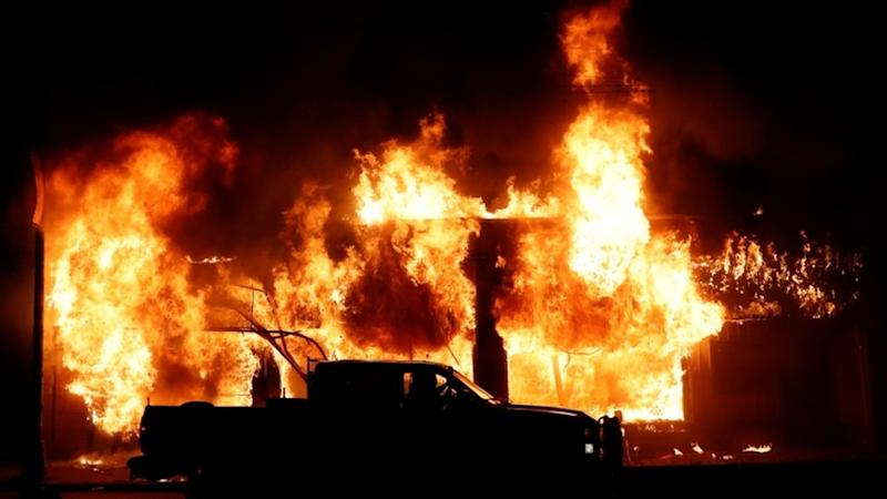 A car is seen in front of a fire during a demonstration against the death in Minneapolis