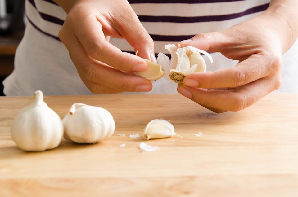 Woman peeling garlic by hand for cooking