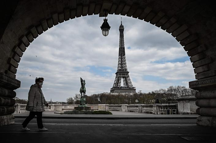 A woman wearing a protective mask walks on the Bir-Hakeim bridge in front of the Eiffel Tower in Paris on April 2, 2020.