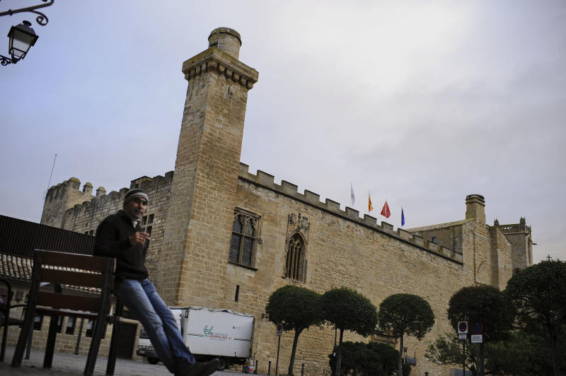 A man rests  beside at parador hotel of Principe de Viana, in Olite, northern  Spain on Friday, Dec. 7, 2012. Employees of Spain's premium hotel chain Parador, a state-run group that uses castles, monasteries and palaces, are holding a two-day strike to protest job cuts and possible closures. The Parador hotels group, which started in 1928, says a drop in demand could leave it with accumulated losses of euro107 million ($140 million) by the end of the year. It intends to cut 644 jobs out of a workforce of 4,400. (AP Photo/Alvaro Barrientos)