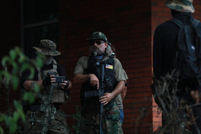 A man with a rifle stands among other far-right supporters during a rally on August 15, 2020 near the downtown of Stone Mountain, Georgia. (Photo by Lynsey Weatherspoon/Getty Images)