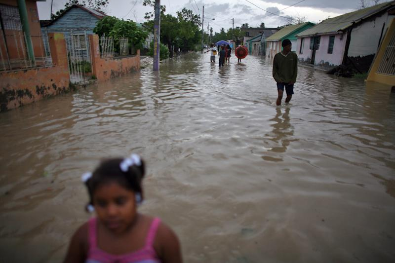 People walk thru flooded streets after Tropical Storm Isaac hit in Barahona, Dominican Republic, Saturday, Aug. 25, 2012. Forecasters said Isaac could dump as much as eight to 12 inches (30 centimeters) and even up to 20 inches (51 centimeters) on Hispaniola, which is shared by Haiti and the Dominican Republic, as well as produce a storm surge of up to 3 feet (0.9 meters). (AP Photo/Ricardo Arduengo)