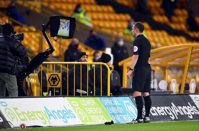 Match referee Stuart Attwell checks the pitch side monitor for a VAR penalty decision at Molineux
